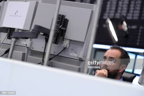A financial trader watches data screens at the Frankfurt Stock Exchange operated by Deutsche Boerse AG as the UK triggers Article 50 of the Lisbon...