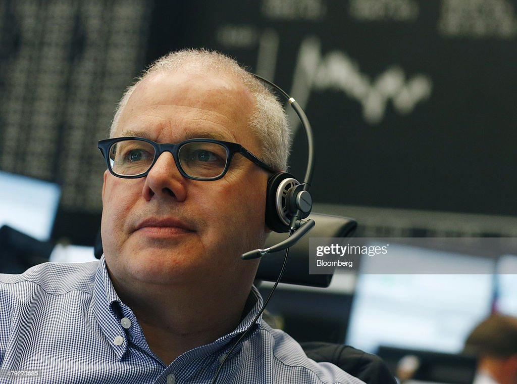 A financial trader works at his desk against the background of the DAX Index curve at the Frankfurt Stock Exchange in Frankfurt, Germany, on Monday, March 17, 2014. European stocks advanced, following their biggest weekly drop since January, as companies from RWE AG to Vodafone Group Plc rose amid renewed merger-and-acquisition activity. Photographer: Ralph Orlowski/Bloomberg via Getty Images