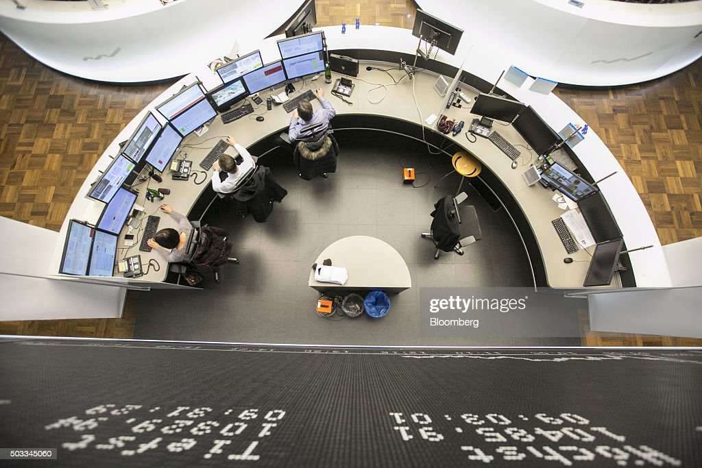 Financial traders monitor computer screens below the DAX Index curve at the Frankfurt Stock Exchange in Frankfurt Germany on Monday Jan 4 2016...