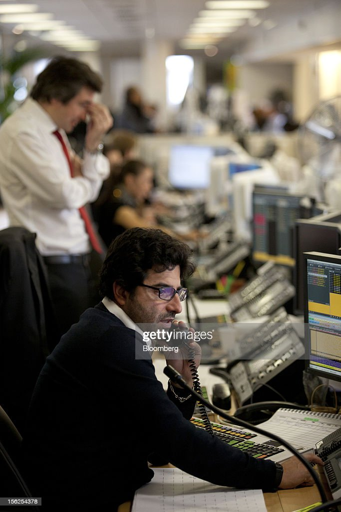 Financial traders monitor data as they work at Aurel BGC's brokerage in Paris, France, on Monday, Nov. 12, 2012. European stocks fluctuated between gains and losses as finance ministers prepared to discuss Greek aid after the country's lawmakers approved the 2013 budget. Photographer: Balint Porneczi/Bloomberg via Getty Images