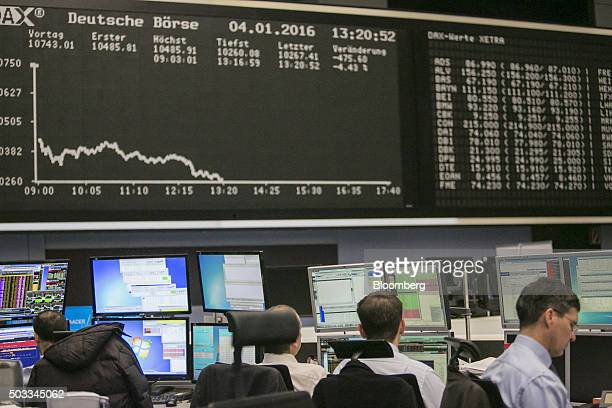 Financial traders monitor data below the DAX Index curve on the first day of 2016 trading at the Frankfurt Stock Exchange in Frankfurt Germany on...