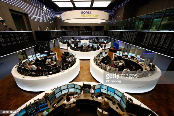 Financial traders monitor data on computer screens as the DAX Index curve is seen beyond at the Frankfurt Stock Exchange in Frankfurt Germany on...