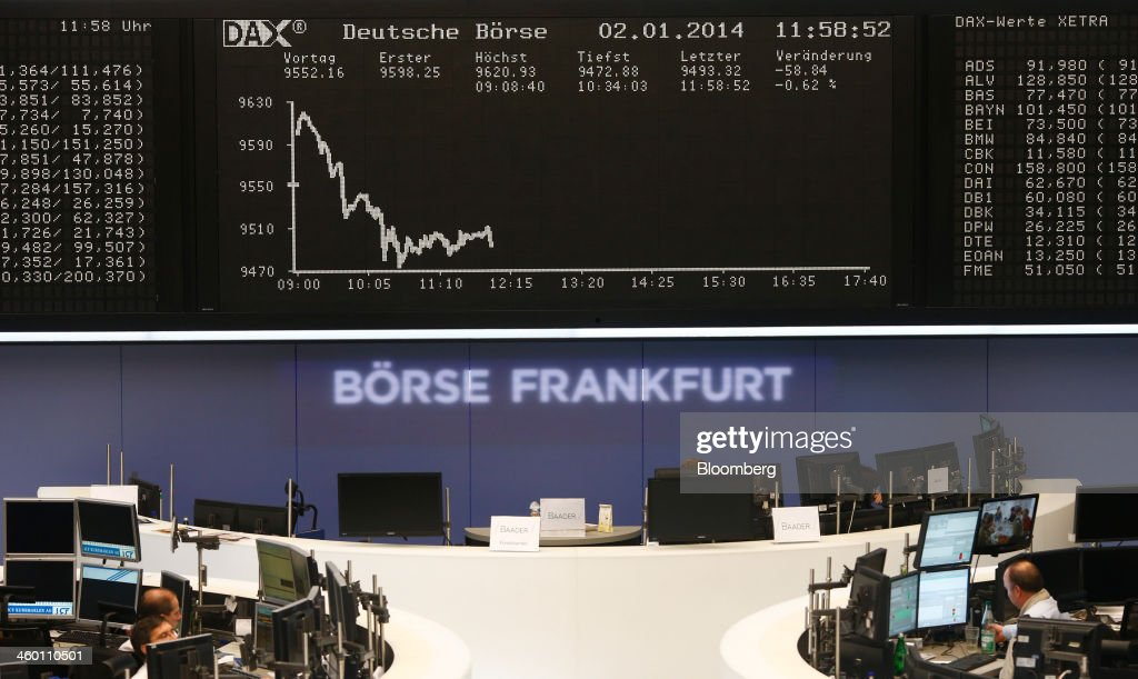 Financial traders monitor data on computer screens as the DAX Index curve is seen beyond at the Frankfurt Stock Exchange in Frankfurt, Germany, on Thursday, Jan. 2, 2014. Most German stocks fell on the first day of trading in 2014, following an annual gain for the benchmark DAX Index, as data showed manufacturing in Europe's largest economy expanded for a sixth month. Photographer: Ralph Orlowski/Bloomberg via Getty Images