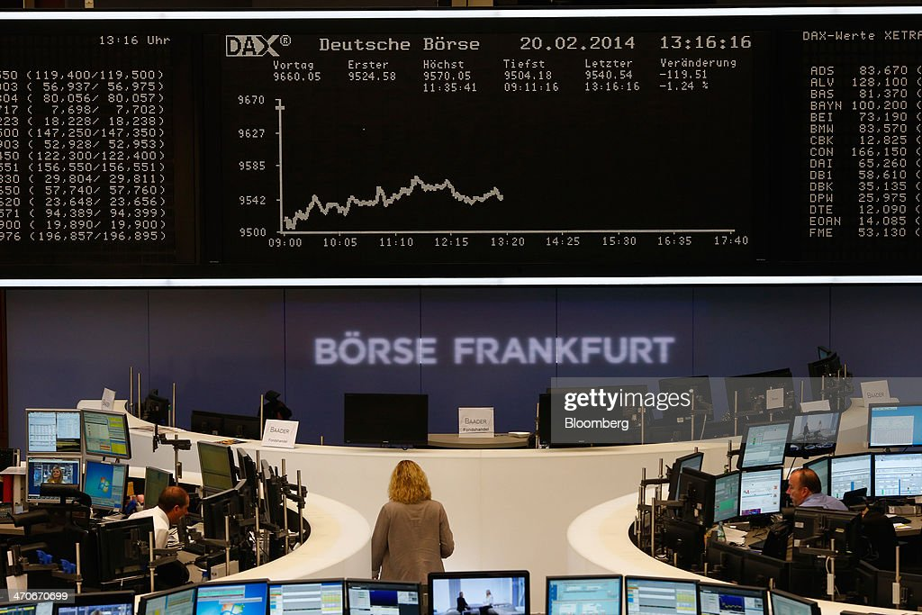 Financial traders monitor data on computer screens as the DAX Index curve is seen beyond at the Frankfurt Stock Exchange in Frankfurt, Germany, on Thursday, Feb. 20, 2014. Deutsche Boerse AG plans to set up a clearinghouse in Singapore to compete with Singapore Exchange Ltd. and IntercontinentalExchange Group Inc. as the owner of the Frankfurt Stock Exchange and the Eurex futures market seeks to benefit from new financial regulations. Photographer: Ralph Orlowski/Bloomberg via Getty Images