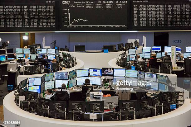 Financial traders monitor data on computer screens as the DAX Index curve is displayed on an electronic board beyond at the Frankfurt Stock Exchange...