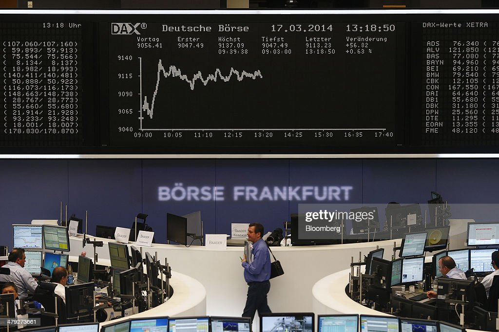 Financial traders monitor data on computer screens as the DAX Index curve is seen beyond at the Frankfurt Stock Exchange in Frankfurt, Germany, on Monday, March 17, 2014. European stocks advanced, following their biggest weekly drop since January, as companies from RWE AG to Vodafone Group Plc rose amid renewed merger-and-acquisition activity. Photographer: Ralph Orlowski/Bloomberg via Getty Images
