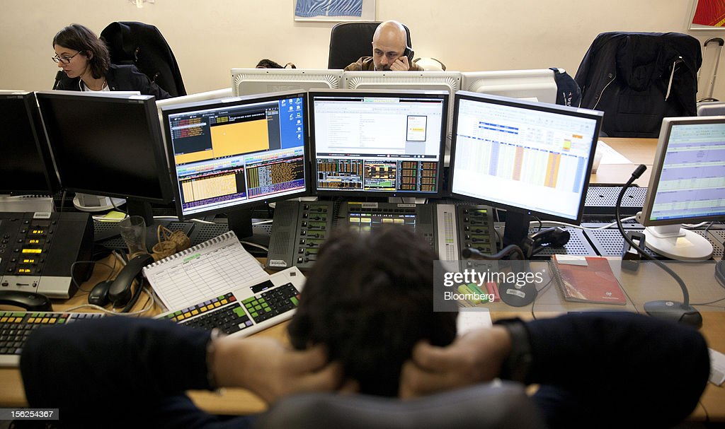 Financial traders monitor data on computer screens at Aurel BGC's brokerage in Paris, France, on Monday, Nov. 12, 2012. European stocks fluctuated between gains and losses as finance ministers prepared to discuss Greek aid after the country's lawmakers approved the 2013 budget. Photographer: Balint Porneczi/Bloomberg via Getty Images