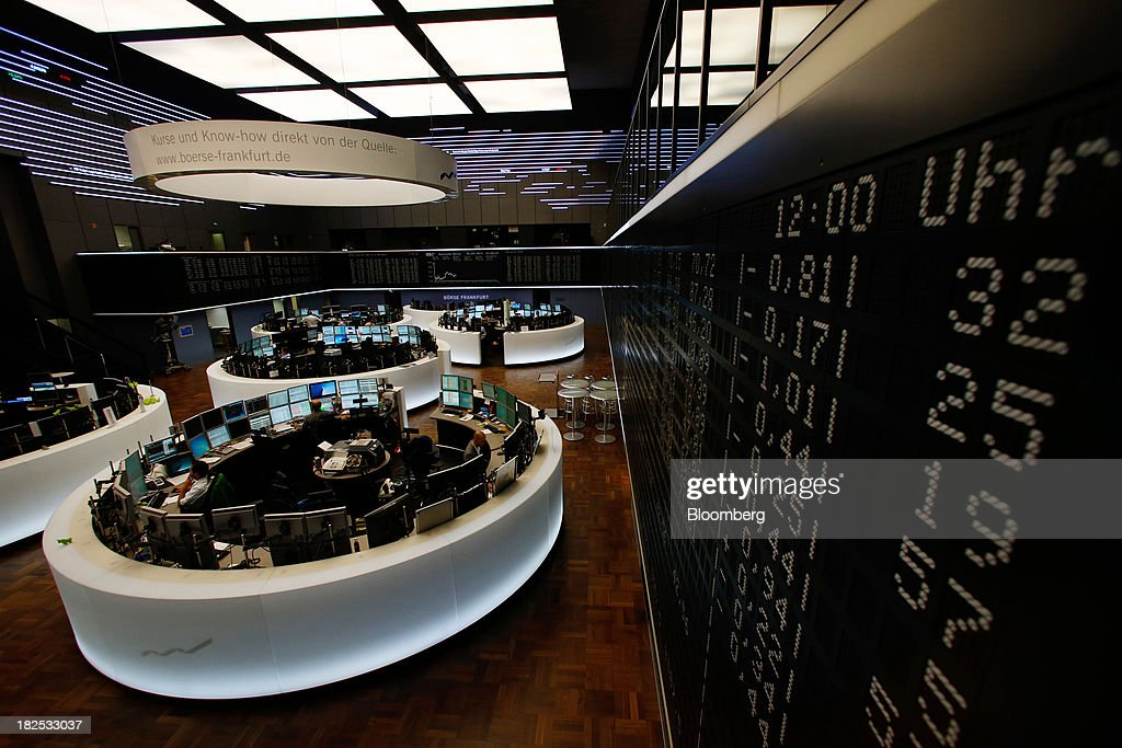 Financial traders monitor data on computer screens beneath a display of the DAX Index curve at the Frankfurt Stock Exchange in Frankfurt, Germany, on Monday, Sept. 30, 2013. Global stocks fell, trimming their biggest quarterly gain since the start of 2012, while the Japanese yen strenghtened before a potential U.S. government shutdown. Photographer: Ralph Orlowski/Bloomberg via Getty Images