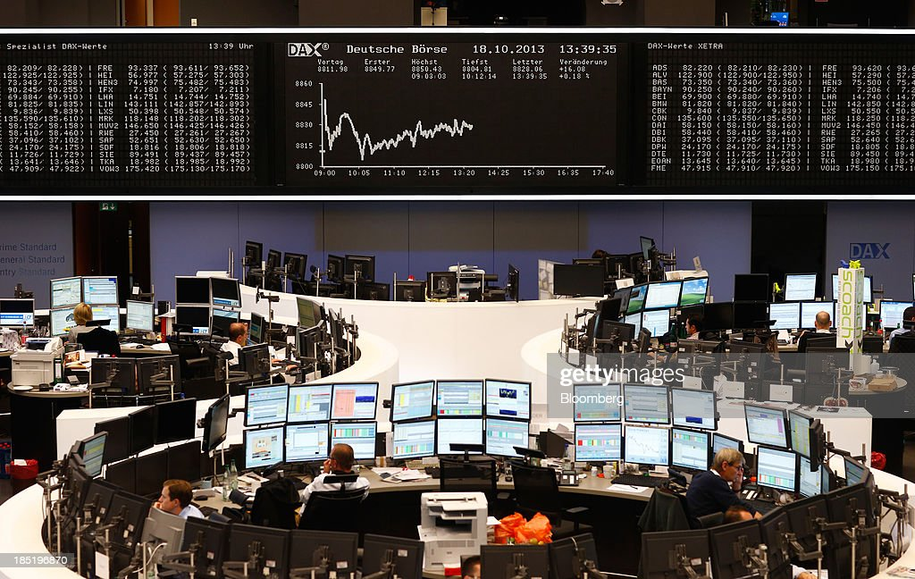 Financial traders monitor data on computer screens beneath a display of the DAX Index curve at the Frankfurt Stock Exchange in Frankfurt, Germany, on Friday, Oct. 18, 2013. Global stocks rose for a third day, extending a five-year high, and copper climbed after China's economic growth quickened. Photographer: Ralph Orlowski/Bloomberg via Getty Images