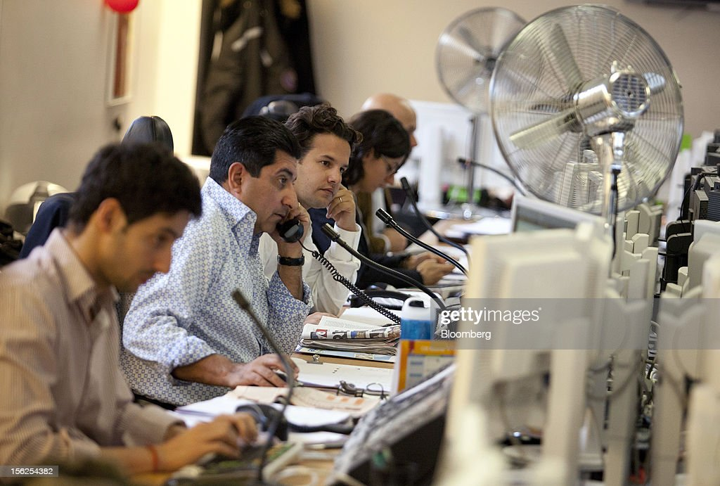 Financial traders react to data on their computer screens Aurel BGC's brokerage in Paris, France, on Monday, Nov. 12, 2012. European stocks fluctuated between gains and losses as finance ministers prepared to discuss Greek aid after the country's lawmakers approved the 2013 budget. Photographer: Balint Porneczi/Bloomberg via Getty Images
