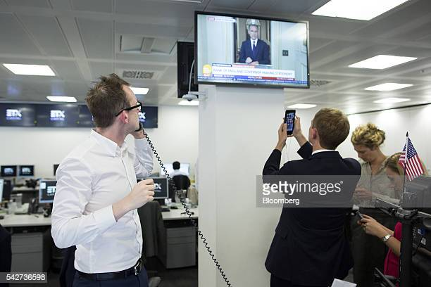 Financial traders react to the European Union referendum vote and watch a television news broadcast by Mark Carney governor of the Bank of England at...