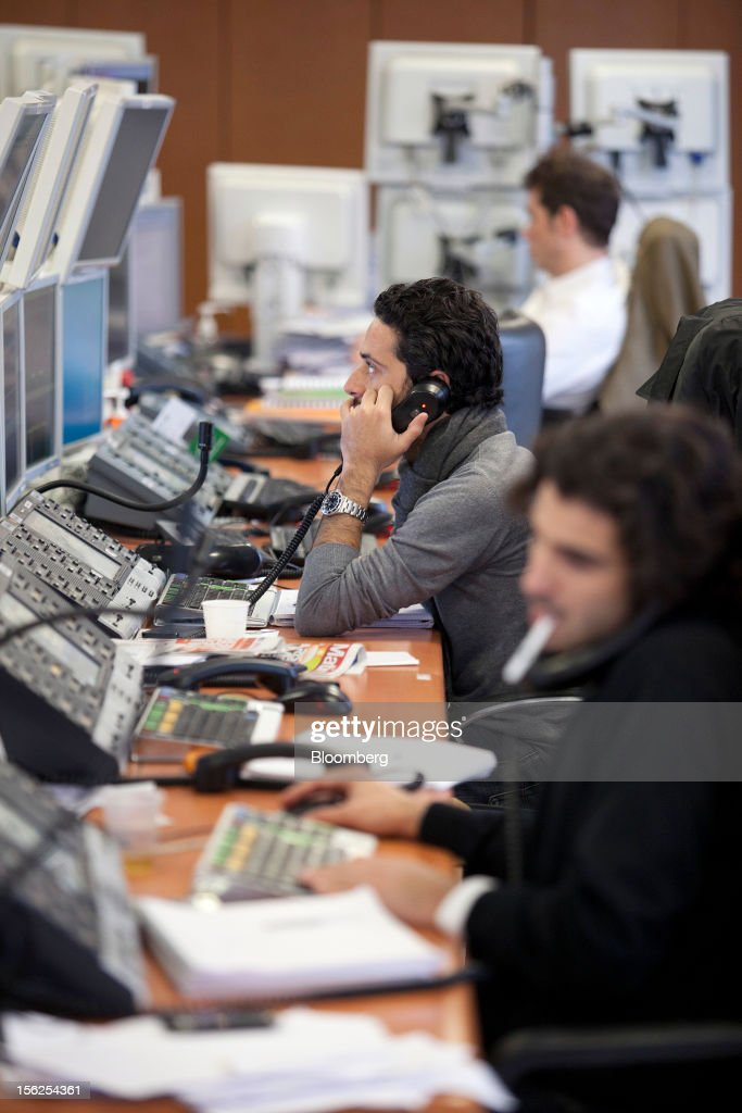 Financial traders use telephones as they monitor data on their computer screens at Aurel BGC's brokerage in Paris, France, on Monday, Nov. 12, 2012. European stocks fluctuated between gains and losses as finance ministers prepared to discuss Greek aid after the country's lawmakers approved the 2013 budget. Photographer: Balint Porneczi/Bloomberg via Getty Images