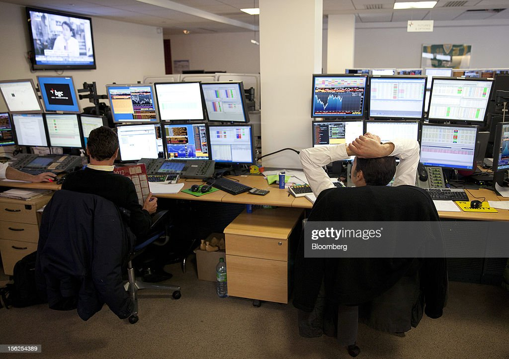Financial traders work from their desks at Aurel BGC's brokerage in Paris, France, on Monday, Nov. 12, 2012. European stocks fluctuated between gains and losses as finance ministers prepared to discuss Greek aid after the country's lawmakers approved the 2013 budget. Photographer: Balint Porneczi/Bloomberg via Getty Images
