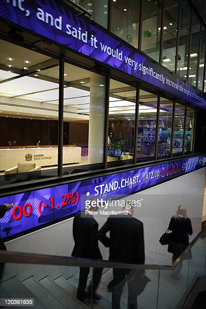 Financial workers walk below screens showing stock price falls at The London Stock Exchange on August 5 2011 in London England The Eurozone debt...