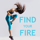 Beautiful young fit modern dancer lady in blue sportswear warming up, working out, dancing with her long hair flying, full length, studio image on gray background. Motivational phrase 'Find your fire'