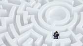 Puzzled young businessman standing in white labyrinth