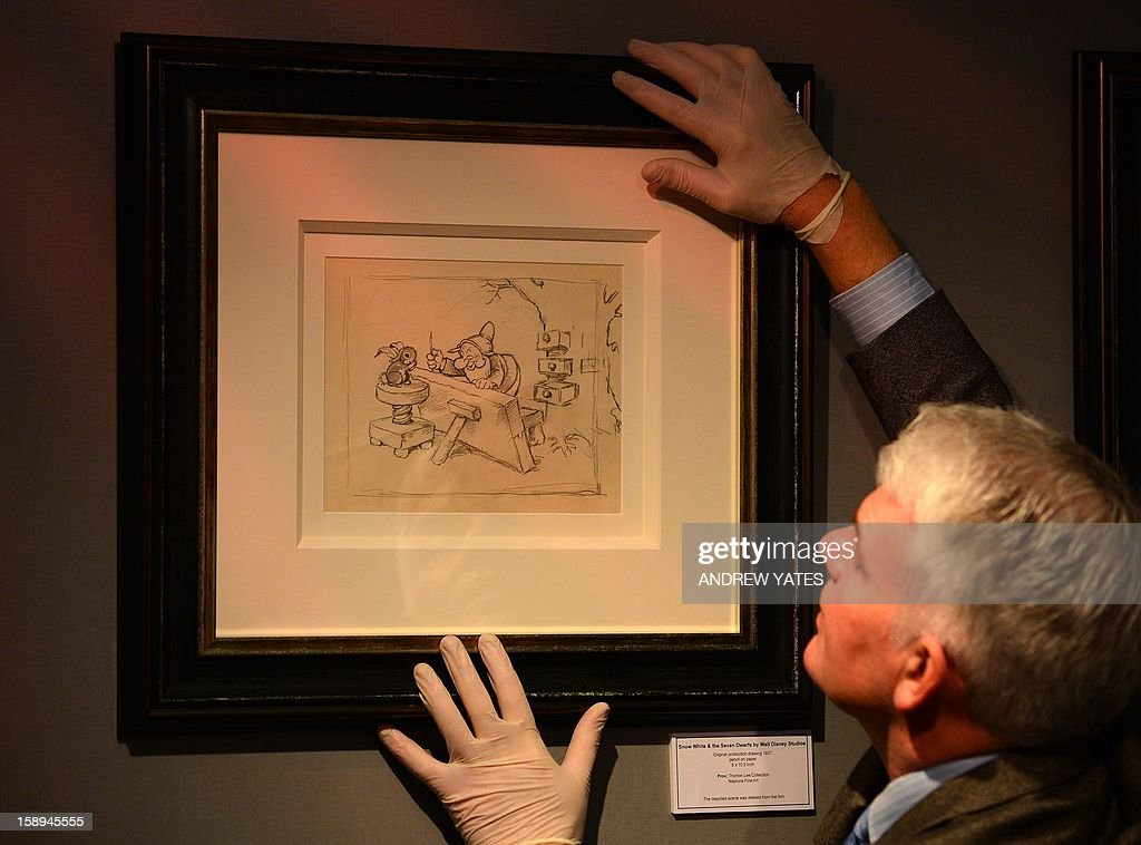 Fine art and antiques consultant Duncan Phillips hangs a never-before-seen original artwork pencil drawing from the 1937 Walt Disney 'Snow White and the Seven Dwarfs' film at the Tatton Park fine arts and antiques fair at Tatton Park in Knutsford, north-west England, on January 4, 2013. The drawing is from the collection of a well-known storyboard artist from the 1930s and 40s and is on sale at a gallery in Derbyshire.