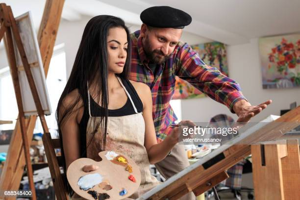 Fine art painter and female apprentice working in atelier