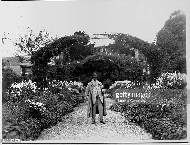 Fine art painter Claude Monet stands on a walkway near a trellis in his garden at Giverny