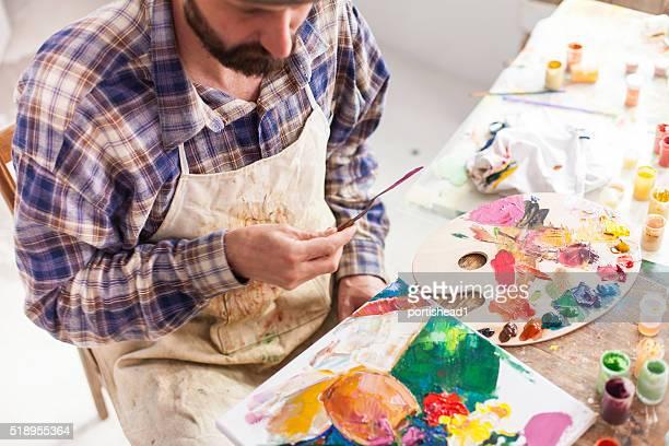 Fine art painter creating new artwork in his studio.