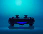 Fine art presentation of a video game controller or joystick on a graduated colorful blue background with copy space and reflection or shadow