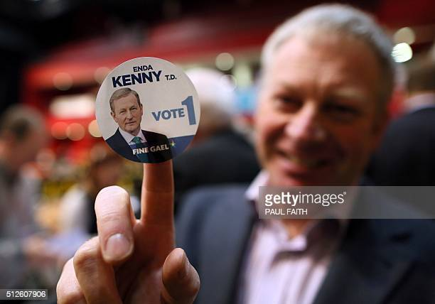 A Fine Gael supporter holds up a badge showing Enda Kenny as counting begins in the home town of Fine Gael party leader Enda Kenny Castlebar in...
