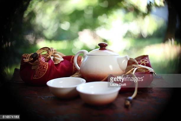 Fine porcelain tea set on silk cloth in garden