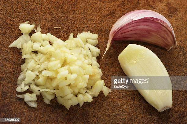 Finely chopped garlic on a wooden cutting board