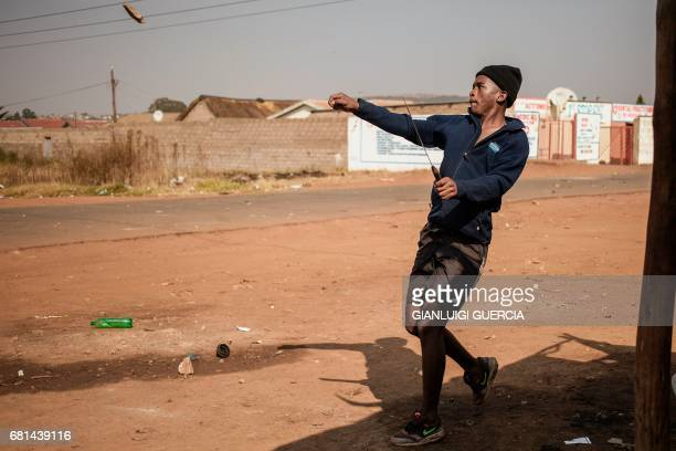 Finetown residents hurl stones at the South African police during clashes amid a protest for better housing on May 10 2017 in Ennerdale south of...