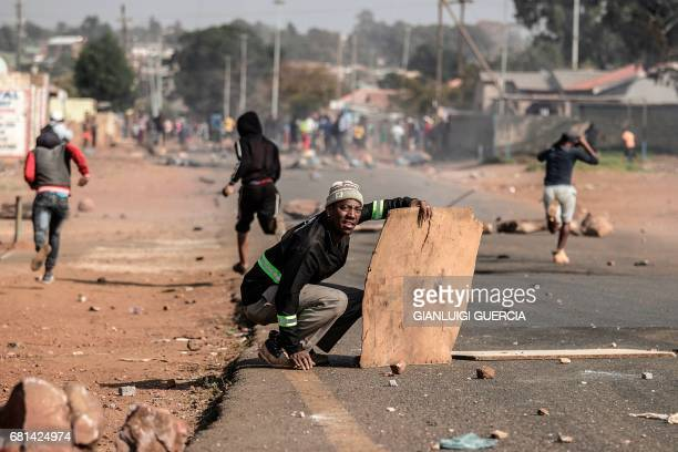 TOPSHOT Finetown residents run and hurl stones at South African police during clashes amid a protest for better housing on May 10 2017 in Ennerdale...