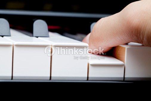Finger on piano : Stock Photo