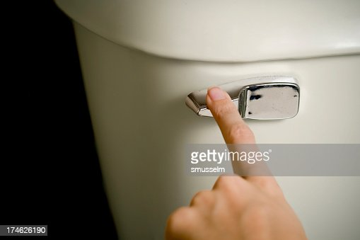 Finger on the toilet handle about to flush