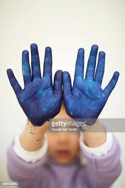 Finger painting girl with blue hands