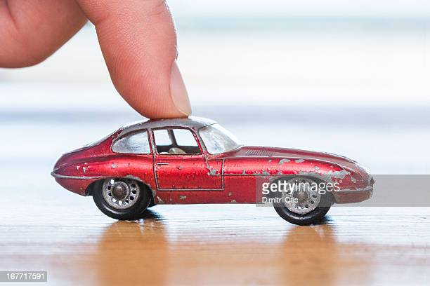Finger placed on red aged toy car