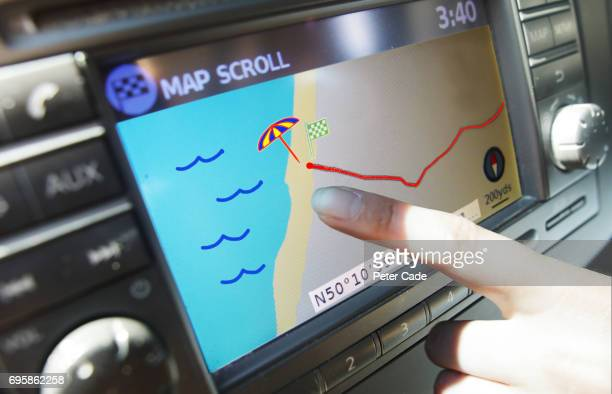 finger pointing at beach location on satellite navigation