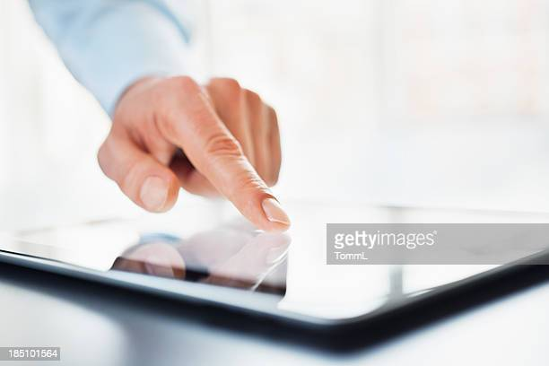 Doigt pointant sur tablette numérique.