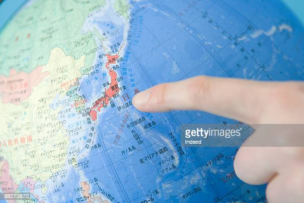 Finger pointing toward Japan on globe