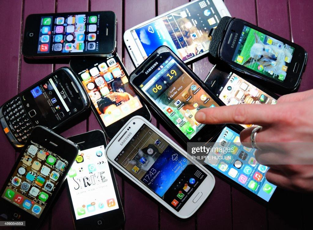 A finger points at smartphones on December 25, 2013 in Dinan, northwestern France.