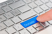 A finger press blue Donate button on laptop keyboard.