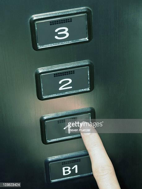 Finger pressing elevator floor button