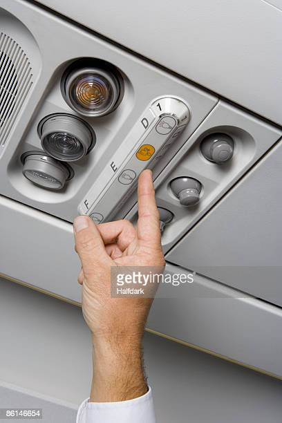 A finger pressing the call button on an airplane