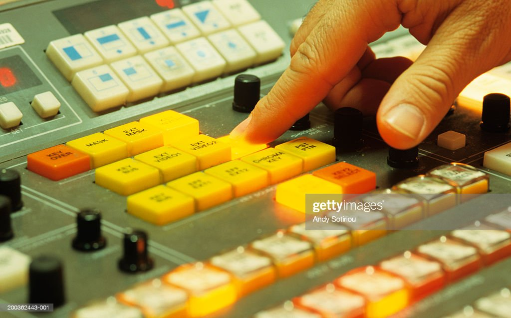 Finger pushing button on Video Editing desk, TV studios, Spain, close-up : Stock Photo