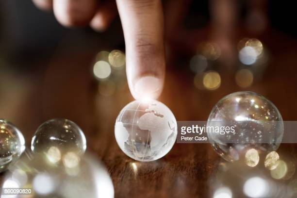 Finger resting on glass globe among other marbles