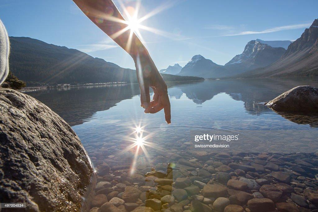 Dito tocca la superficie di un lago di montagna : Foto stock