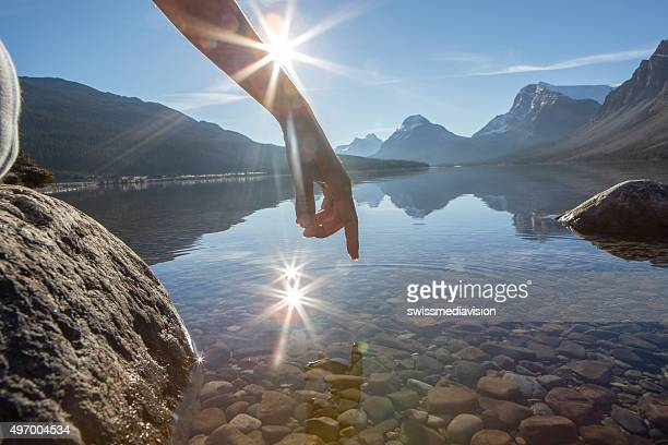 Dito tocca la superficie di un lago di montagna