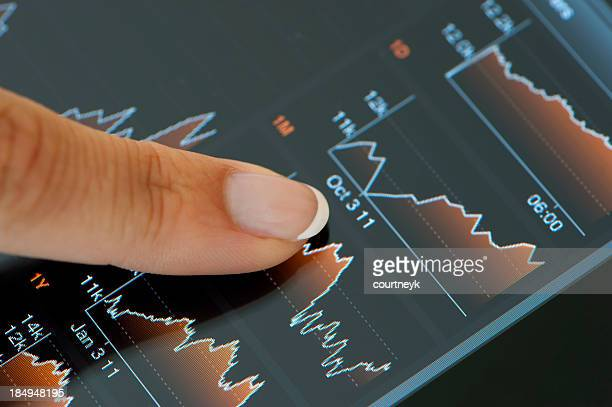 Finger touching a digital tablet with financial data