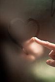 Finger writing heart on steamy mirror