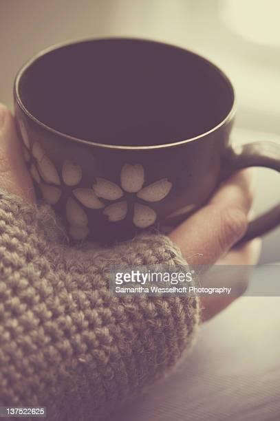 Fingerless gloves and hot tea in mug