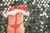 Fingers art of couple celebrates Christmas in new year hats. Toned image.