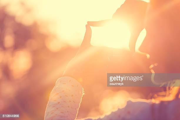 Doigts sur le soleil au coucher du soleil.